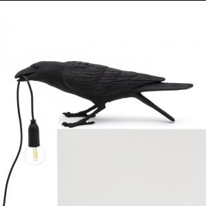 """Lampa i form av en svart fågel som håller lampsladden i näbben. Själva lampan är en """"naken lampa"""" som hänger längst ut på sladden. Bird Lamp finns hos Magasin 11."""